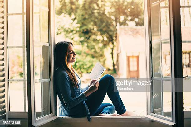 Reading a book at the window