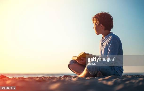 reading a book on the beach at sunset - poetry literature stock pictures, royalty-free photos & images