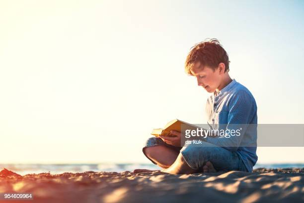 Reading a book on the beach at sunset