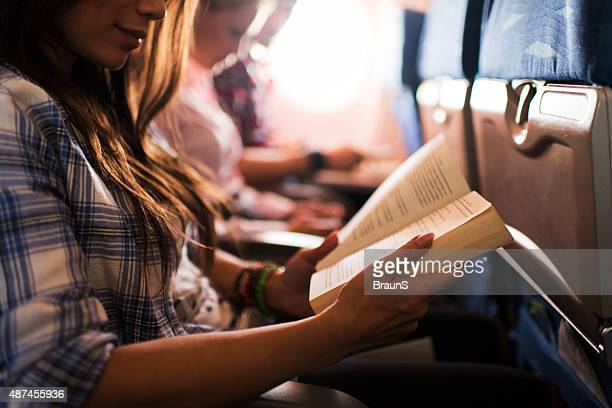 Reading a book while travelling by airplane.
