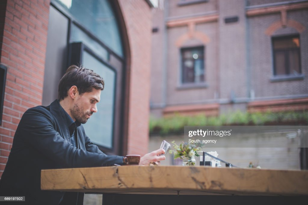 Reading a newspapers at the sidewalk cafe : Stock Photo