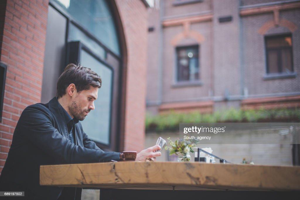 Lendo um jornal no café calçada : Foto de stock