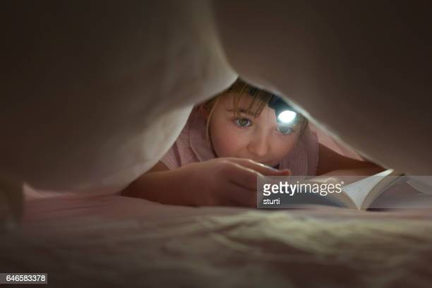 reading at bedtime with head torch - forbidden stock pictures, royalty-free photos & images