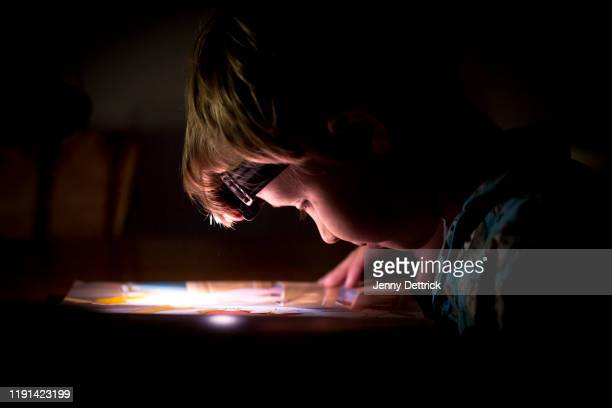 reading by torchlight - blackout picture stock pictures, royalty-free photos & images