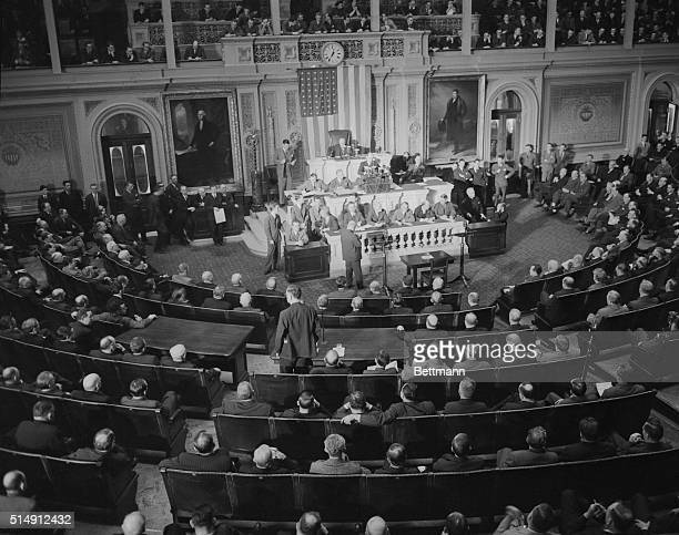 Reading Clerk Irving W. Swanson reads the Resolution for War against Germany here on December 11th, to an attentive House of Representatives. The...