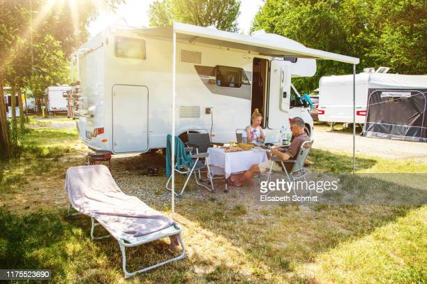 reading couple in front of motorhome - camper trailer stock pictures, royalty-free photos & images