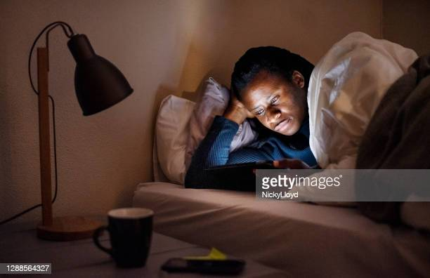 reading e-book on a digital tablet at night - nl ebook stock pictures, royalty-free photos & images
