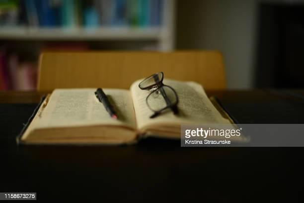 reading glasses and a pen on an old vintage dictionary - litteratur bildbanksfoton och bilder