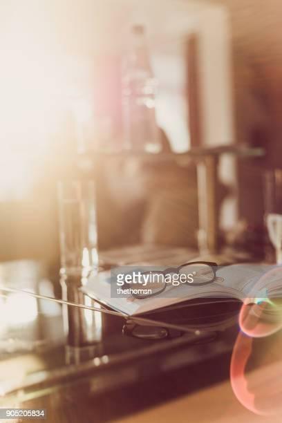 Reading glasses on open book on kichten worktop