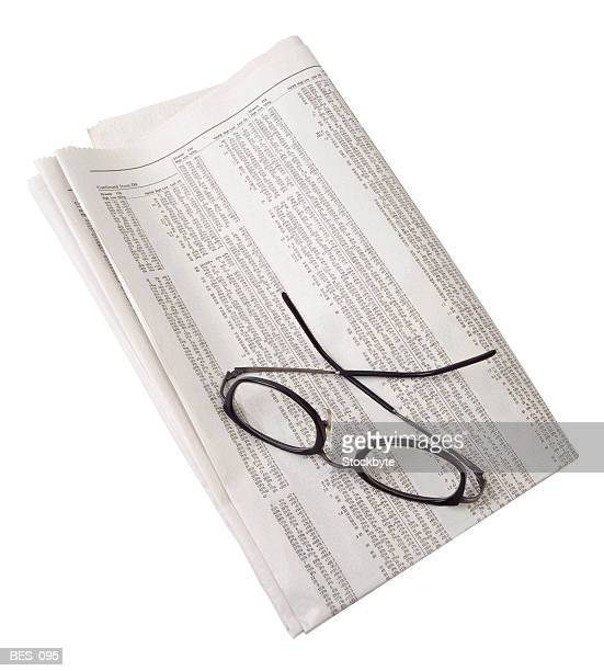 Reading glasses resting on folded newspaper stock listings