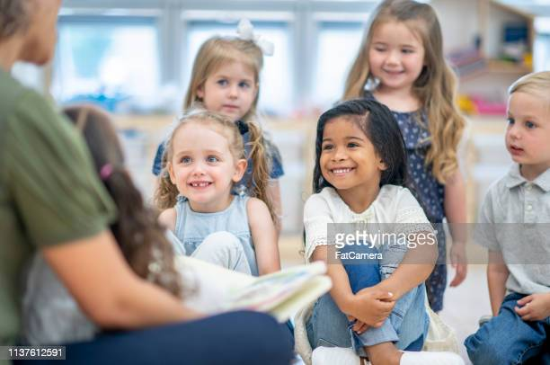 reading in daycare - preschool age stock pictures, royalty-free photos & images