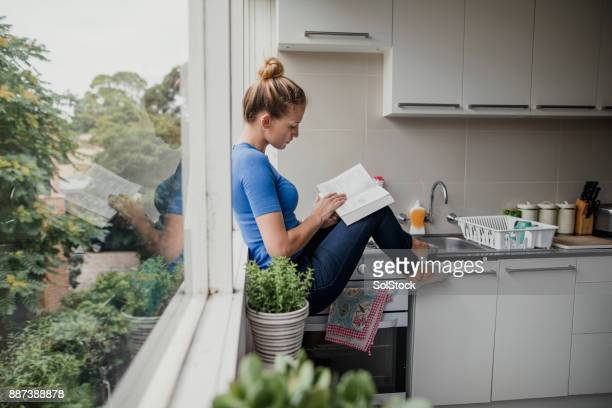 reading in the kitchen - melbourne australia foto e immagini stock