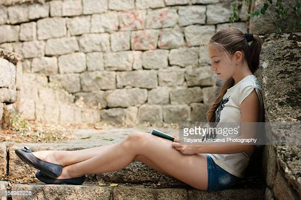 reading in the park - hot pants stock photos and pictures