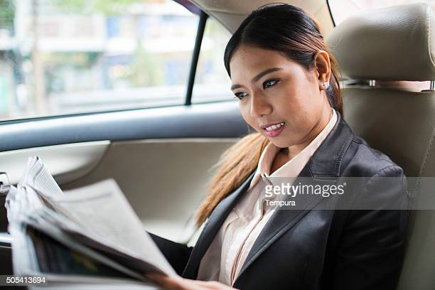 Reading latest news commuting to work on a taxi.