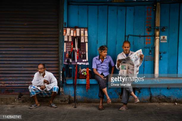 reading newspaper at roadside - hooghly river stock pictures, royalty-free photos & images