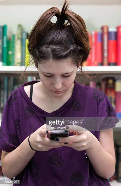 reading on smartphone, ignoring books - black nail polish stock photos and pictures