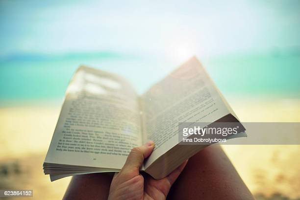 reading paper book on the beach from personal perspective