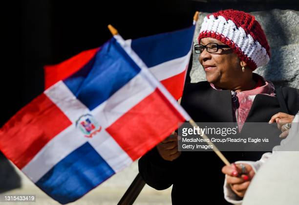 Reading resident Esperanza Arias waves her flag during a celebration for Dominican Republic Independence Day outside City Hall. Photo by Natalie Kolb...
