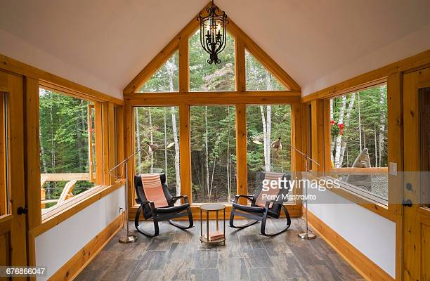 Reading room with ceramic tile floor and two black leather rocking chairs in cottage-style log cabin, Quebec, Canada