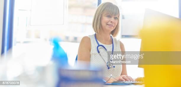 lezing testresultaten op haar computer - huisarts stockfoto's en -beelden