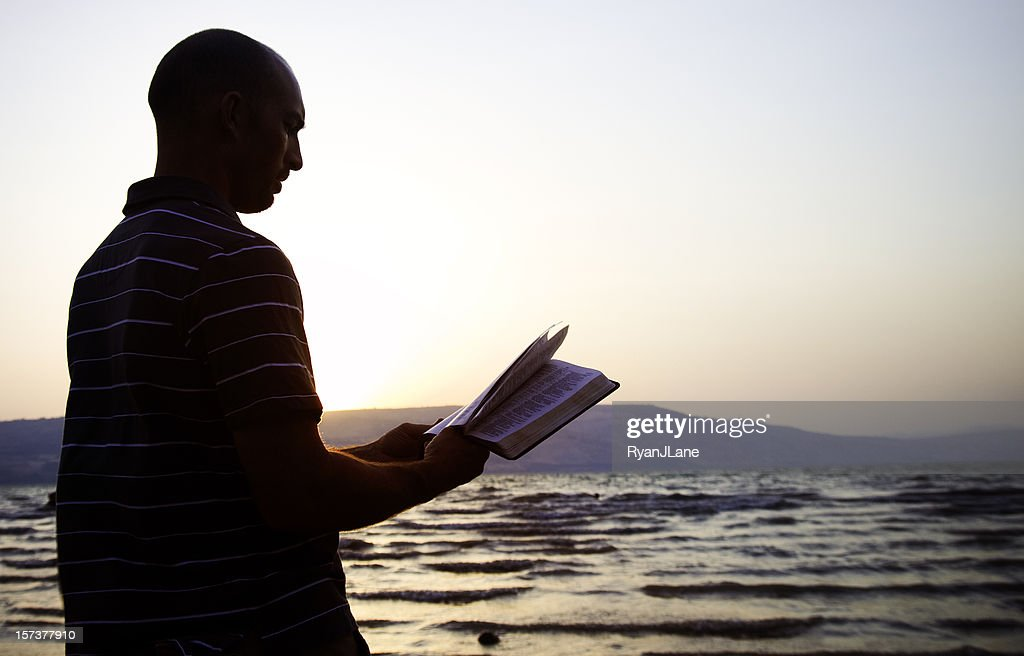 Reading the Bible by Sea of Galilee, Israel : Stock Photo