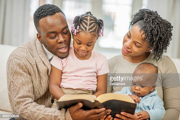 reading the bible together as a family - bible photos stock pictures, royalty-free photos & images