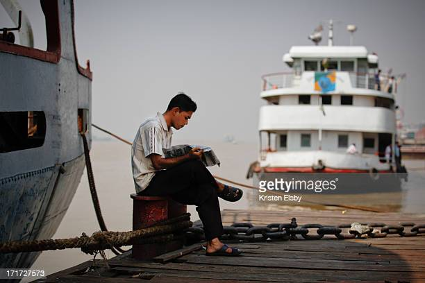 Reading the daily newspaper on the dock, a Burmese man takes a break from working on a boat on the Yangon River.