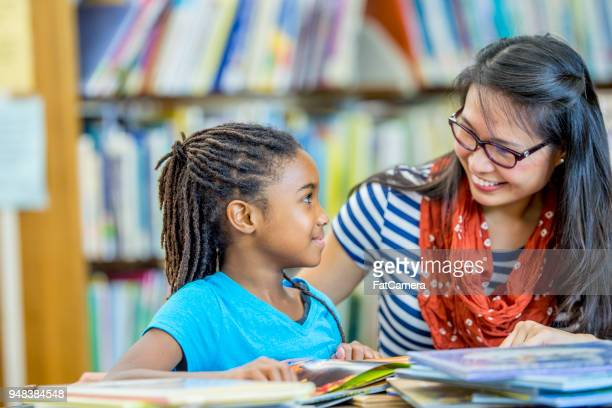 reading together in the library - primary age child stock pictures, royalty-free photos & images