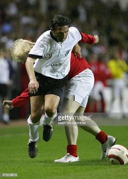 England's Conservative MP Boris Johnson tackles a German opponent as they take part in the charity match England v Germany Legends Match at the...