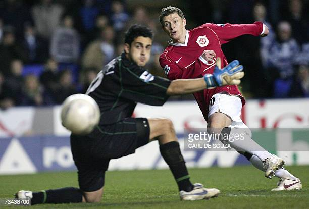 Manchester United's Norwegian striker Ole Gunnar Solskjaer scores past Reading's goalkeeper Adam Federici during their Premiership match at home to...