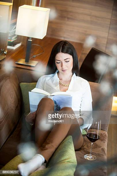 Reading woman sitting in hotel lounge with glass og red wine