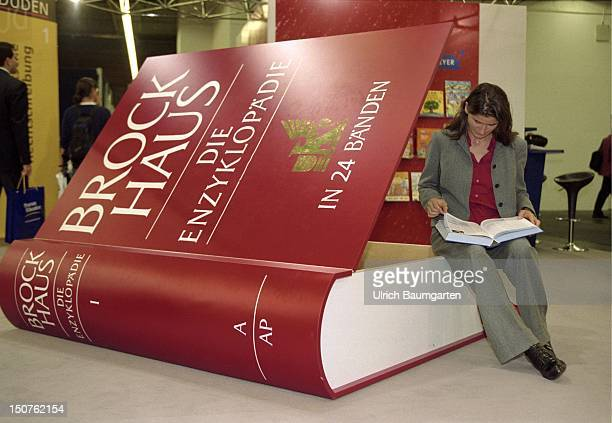 Reading woman sitting on an oversized Brockhaus book during the book fair in Frankfurt