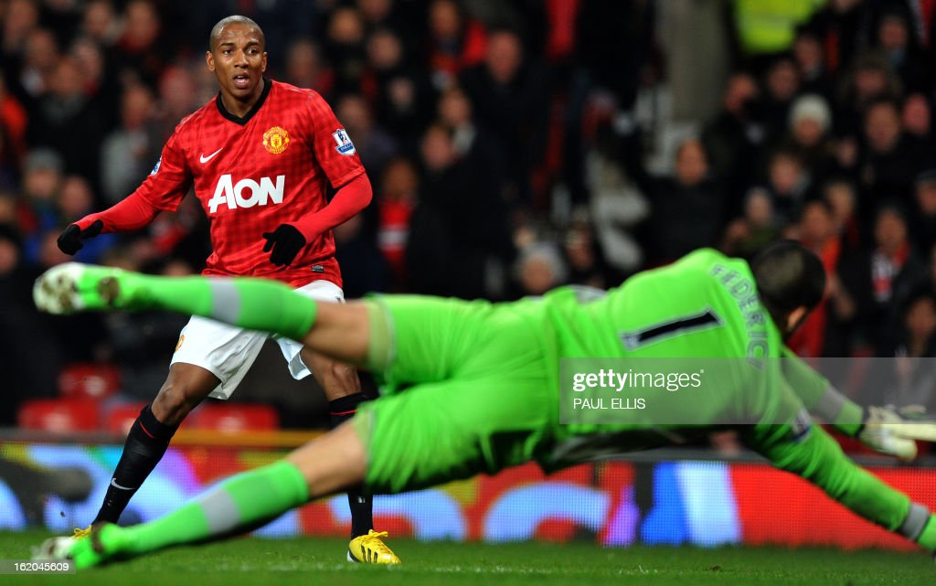 """Reading's Australian goalkeeper Adam Federici (R) dives to block a shot by Manchester United's English midfielder Ashley Young (L) during the English FA Cup fifth round football match between Manchester United and Reading at Old Trafford in Manchester, north west England, on February 18, 2013. USE. No use with unauthorized audio, video, data, fixture lists, club/league logos or """"live"""" services. Online in-match use limited to 45 images, no video emulation. No use in betting, games or single club/league/player publications."""