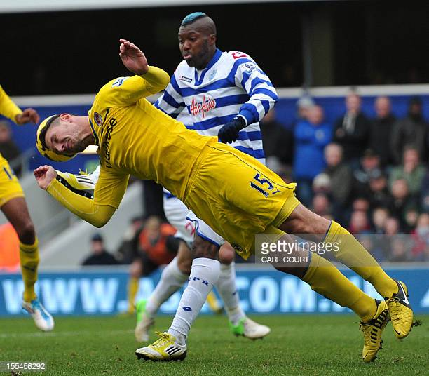Reading's English defender Sean Morrison heads the ball clear from Queens Park Rangers' French striker Djibril Cisse during the English Premier...