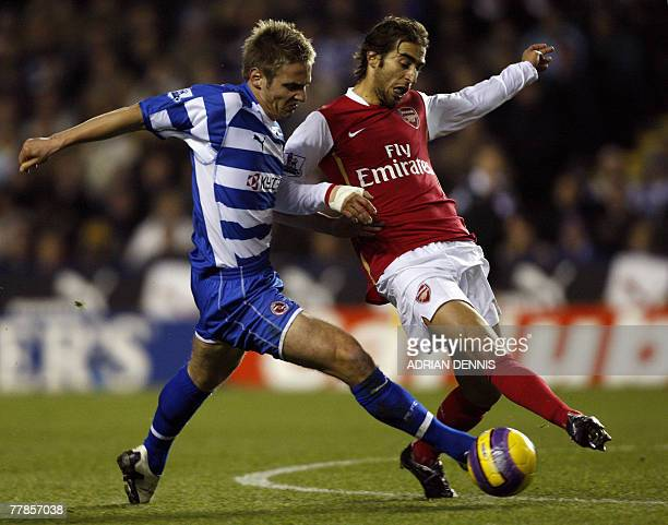 Reading's Kevin Doyle vies for the ball against Arsenal's French player Mathieu Flamini during the Premiership football match at the Madejski Stadium...