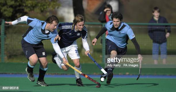 Reading's Stephen Dick and Simon Mnatell challenge with East Grinstead's Matt Gramsbusch during their England Hockey League Premier Division match at...