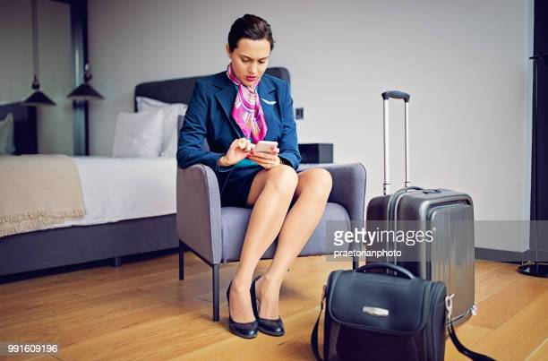 Ready cabin crew member is texting and waiting for her flight in the hotel room