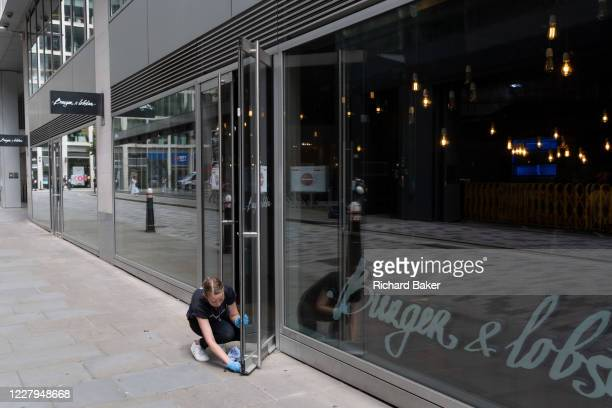 Readying to re-open a burger and lobster restaurant business, a females employee wipes down door surfaces during the Coronavirus pandemic in the City...
