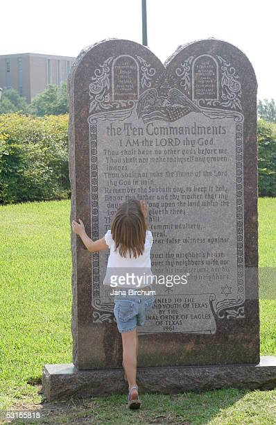 Reagan Taylor age 6 looks at a stone monument of the Ten Commandments outside of the Texas State Capitol June 27 2005 in Austin Texas A sharply...