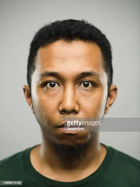 real arabic young man with blank expression - police mugshot stock pictures, royalty-free photos & images