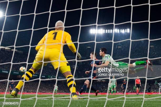 Real Betis' Algerian defender Aissa Mandi dives for the ball beside Valencia's Spanish forward Santi Mina during the Spanish Copa del Rey semifinal...