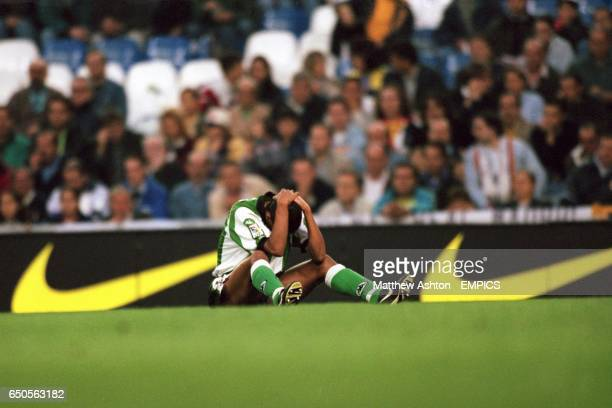 Real Betis' Denilson holds his head after a collision