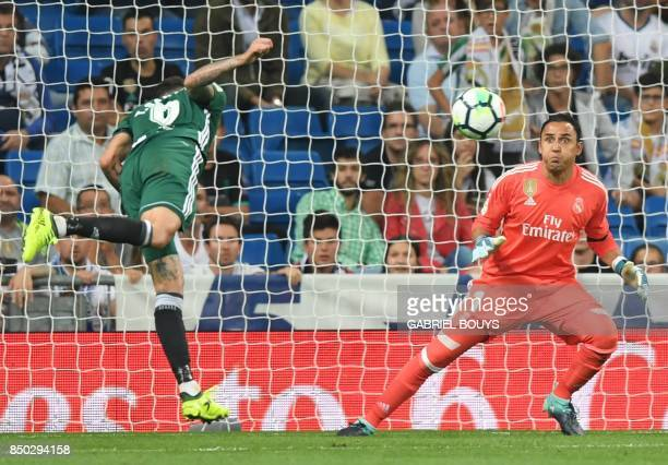 Real Betis' forward from Paraguay Arnaldo Sanabria heads the ball against Real Madrid's goalkeeper from Costa Rica Keylor Navas to score a goal...