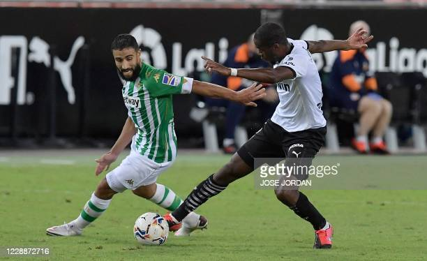 Real Betis' French midfielder Nabil Fekir challenges Valencia's French defender Mouctar Diakhaby during the Spanish League football match between...