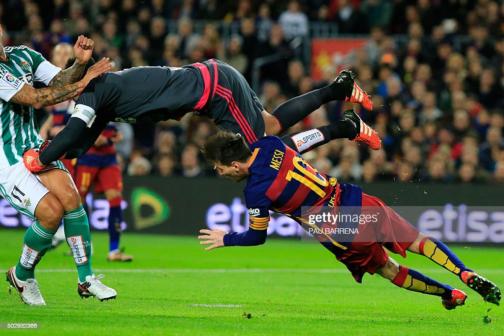 TOPSHOT - Real Betis' goalkeeper Antonio Adan (up) hits Barcelona's Argentinian forward Lionel Messi during the Spanish league football match FC Barcelona vs Real Betis Balompie at the Camp Nou stadium in Barcelona on December 30, 2015.