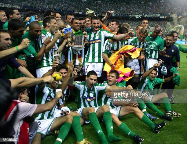 Real Betis players gather to celebrate with the trophy after beating Osasuna in a Kings Cup final on June 11, 2005 at the Calderon Stadium in Madrid,...