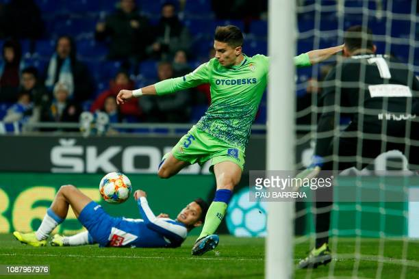 Real Betis' Spanish defender Marc Bartra kicks the ball in front of Espanyol's goalkeeper Roberto during the Spanish Copa del Rey quarterfinal first...