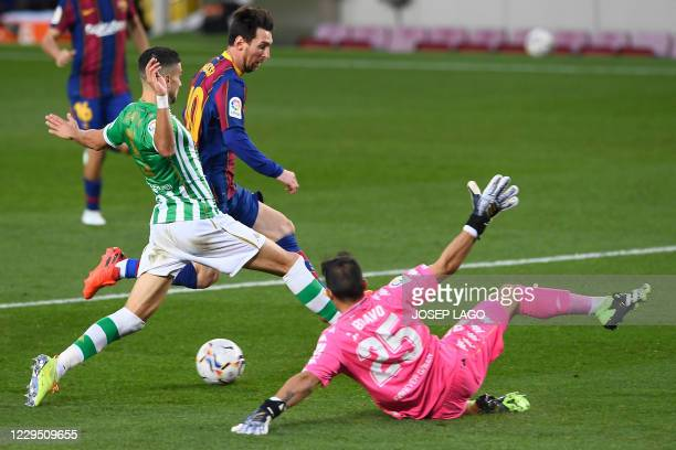 Real Betis' Spanish defender Marc Bartra vies with Barcelona's Argentine forward Lionel Messi during the Spanish League football match between...