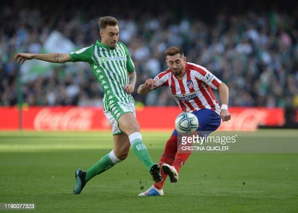 Real Betis' Spanish forward Loren Moron fights for the ball with Atletico Madrid's Mexican midfielder Hector Herrera during the Spanish league...