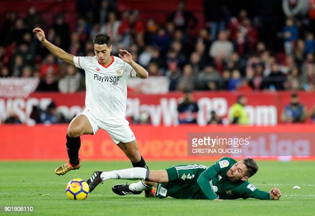 Real Betis' Spanish midfielder Javi Garcia challenges Sevilla's French forward Wissam Ben Yedder during the Spanish league football match between...